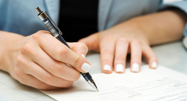 Woman Signing a Forebearance Agreement to Avoid Foreclosure