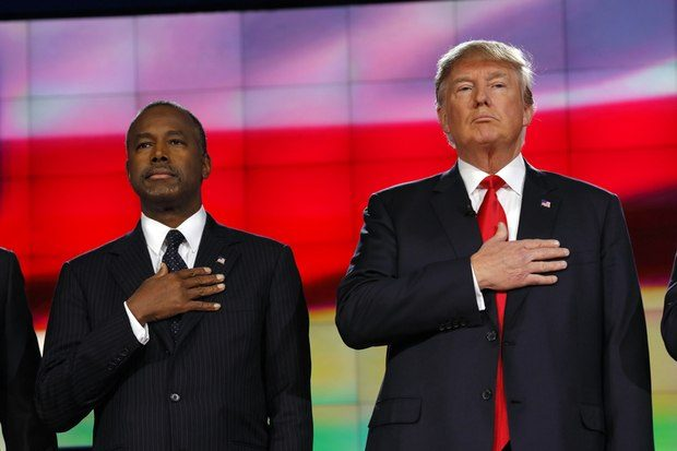 Prsident Elect Donald Trump and neurosurgeon Ben Carson hold hand over heart
